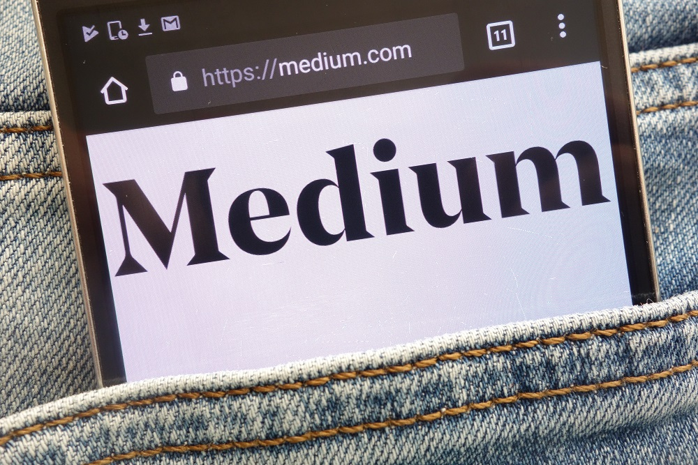 Medium website displayed on smartphone hidden in jeans pocket